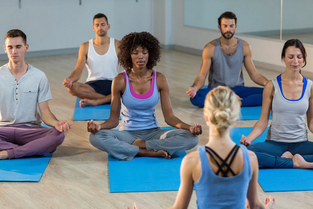 Instructor taking yoga class in fitness studio